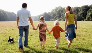family holding hands and walking away from camera in meadow