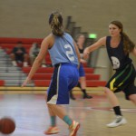 Photo of two students playing basketball