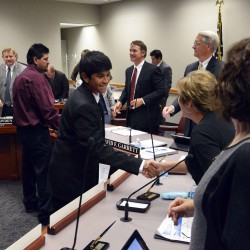 Photo of student and father shaking hands with board of education