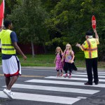 Photo of Utah Jazz player greeting two students crossing street
