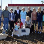 Photo of Winder family posing behind plaque at Granger High