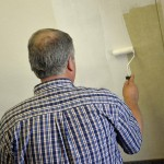 Photo of volunteer painting Kearns Jr. High classroom