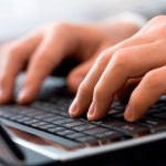 Photo of fingers typing on computer keyboard