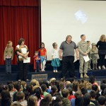 Photo of West Kearns parents and students standing on stage during assembly
