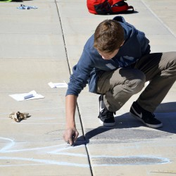Photo of Wasatch Jr High student drawing with sidewalk chalk