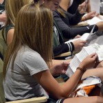 Photo of Olympus High students reading papers in auditorium