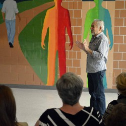 Photo of artist speaking to audience gathered in Decker Lake facility