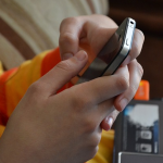 Photo of teen's hands holding smartphone.