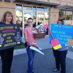 Photo of Diamond Ridge volunteers with custodian appreciation signs