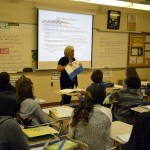 Photo of West Lake teacher speaking to class about WWII soldier's suitcase