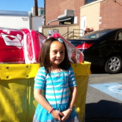 Photo of Whittier Elementary student in front of donated items