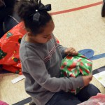Photo of Lincoln Elementary student unwrapping gift