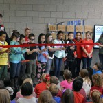 Photo of Armstrong Academy students cutting ribbon for weather station