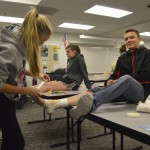 Photo of student wrapping bandages on student volunteer