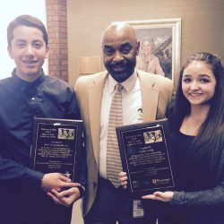 Photo of two students holding award plaques next to West Lake principal