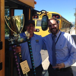 Photo of bus driver receiving trophy from assistant principal