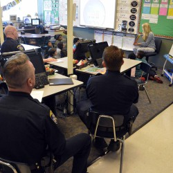 Photo of police officer presenting new book to Wilson Elementary students