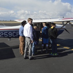 Photo of students and teachers next to airplane