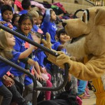 Photo of Kearns High mascot giving high-fives to kindergarteners