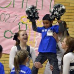 Photo of Kearns High cheerleaders lifting kindergarten student