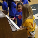 Photo of Kearns Network kindergartener playing piano with Kearns High student