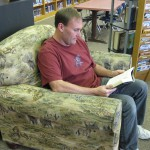 Photo of media specialist reading while sitting in chair