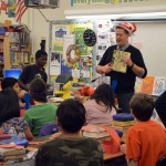 Photo of administrator reading book to Moss Elementary students