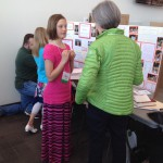 Photo of student explaining science fair project to judge