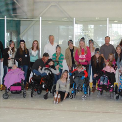 Photo of high school students pushing wheelchair-bound peers on ice rink