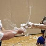 Photo of Whittier volunteers bursting shaving cream-filled balloon