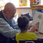Photo of volunteer reading to Redwood Elementary student