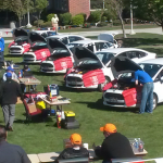 Photo of students working on cars during auto skills competition