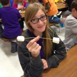 Photo of student holding marshmallow tower piece