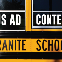 Photo of school bus window with added text 'Bus Ad Contest'