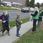 Photo of students receiving treats from volunteers on sidewalk