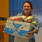 Photo of Skyline High student holding box of donated food