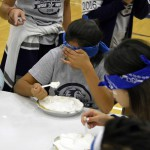 Photo of blindfolded students eating pies