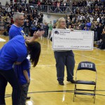Photo of teacher presenting large check to family during assembly