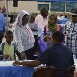 Photo of refugee family receiving information from community table