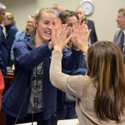 Photo of student giving a high-five to board member