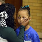 Photo of Kearns High cheerleader painting face of kindergarten student