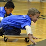 Photo of Kearns Network kindergarten students riding on skateboards