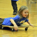Photo of Kearns Network kindergarten student riding on skateboard