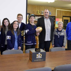 Photo of Skyline High SBOs and former NFL player posing with commemorative football