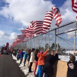 Photo of students holding American flags on overpass