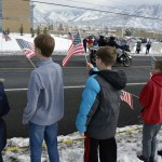 Photo of students standing on sidewalk holding U.S. flags as police pass on street