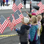 Photo of students standing on sidewalk holding U.S. flags