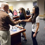 Photo of student athletes shaking hands with members of the board of education