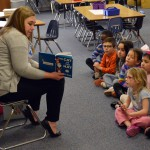 Photo of volunteer reading book to Moss Elementary students