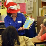 Photo of volunteer reading book to Spring Lane students
